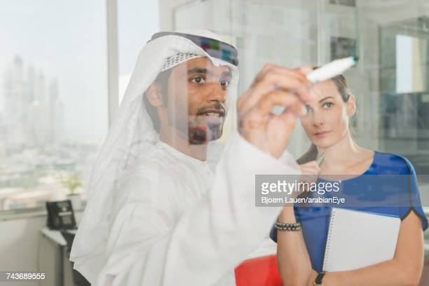 Emirati businessman discussing project with colleague at office.