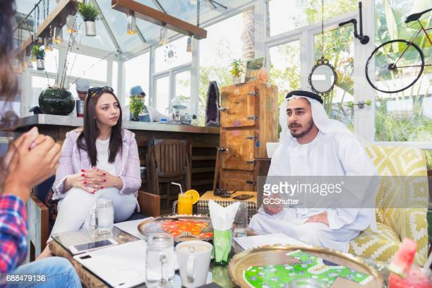 Emirati Businessman meeting a businesswoman and her colleagues at a cafe
