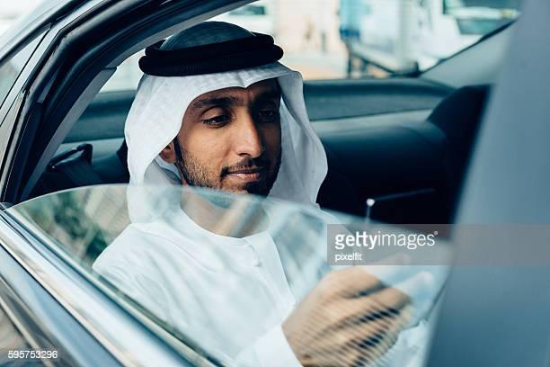 Emirati Businessman with smart phone in a car