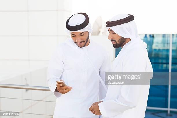 Emirati Businessmen Sharing Information Using Smartphone