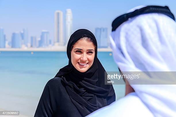 emirati couple talking - muslim woman beach stock photos and pictures