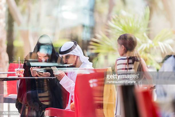 Emirati Couple with Daughter at Outdoor Cafe Checking Smart Phones