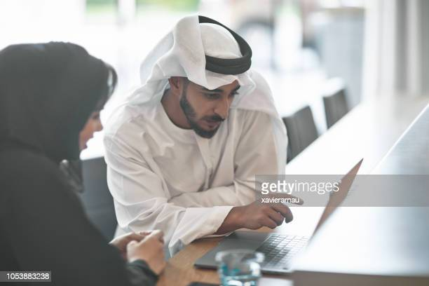 emirati entrepreneurs discussing over laptop - united arab emirates stock pictures, royalty-free photos & images