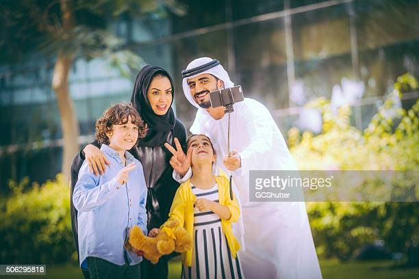Emirati family in a park taking selfie, Dubai, UAE