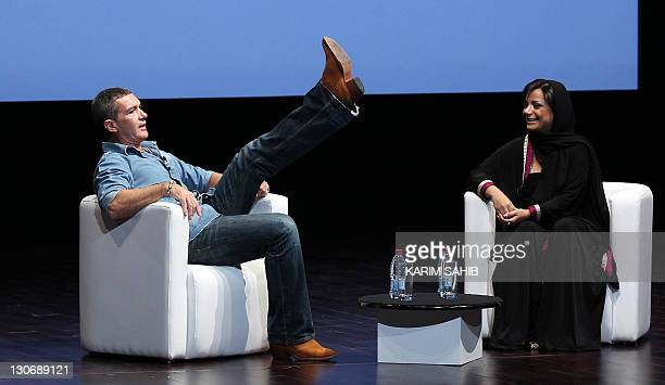 Emirati film director Nayla alKhaja smiles as Spanish film star Antonio Banderas shows off his boots during an interview on the sidelines of the Doha...