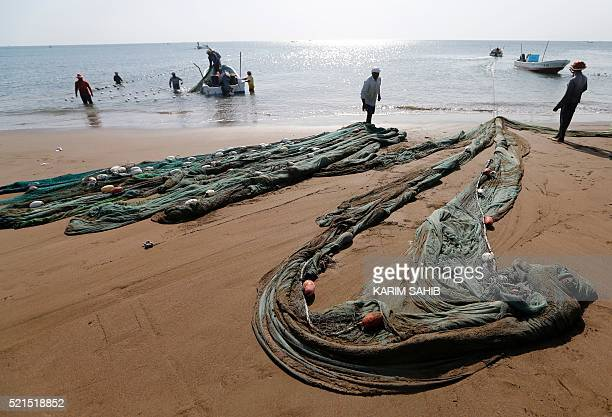 Emirati fishermen sort out their nets on a beach along the coast of the Gulf of Oman in the Emirate of Fujairah on April 16 2016 SAHIB