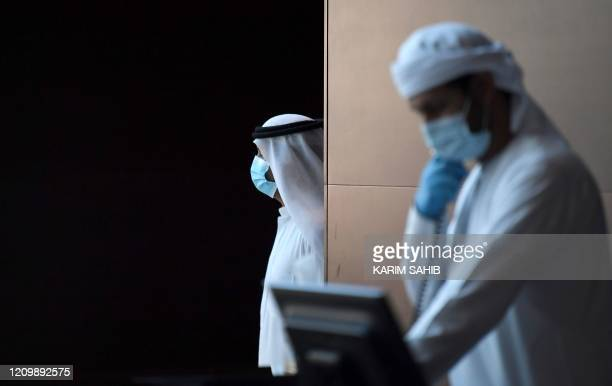Emirati hotel staff wearing protective masks and gloves work at a hotel where families returning to the UAE will stay 14days in quarantine amid the...