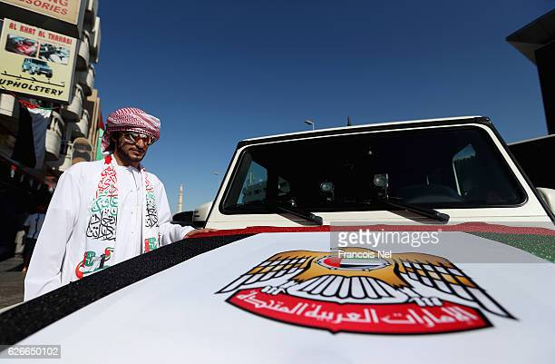 Emirati man stand next to his car decorated with a UAE flag ahead of the 45th UAE National Day on November 30 2016 in Dubai United Arab Emirates