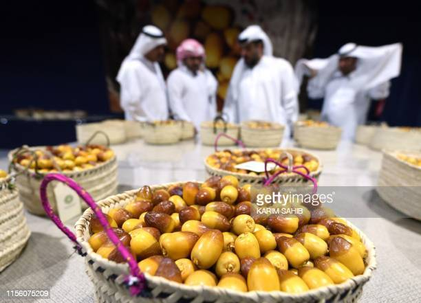 Emirati men check baskets of Dabas and Khalas dates during the annual Liwa Date Festival in the western region of Liwa on July 17, 2019. - The Liwa...