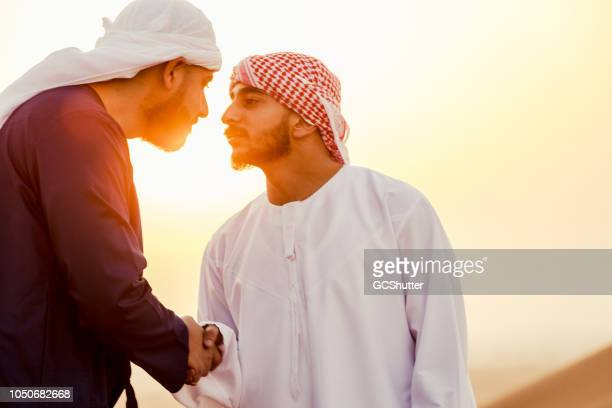 Emirati Men Greeting Each Other at the Sand Dunes during Sunrise
