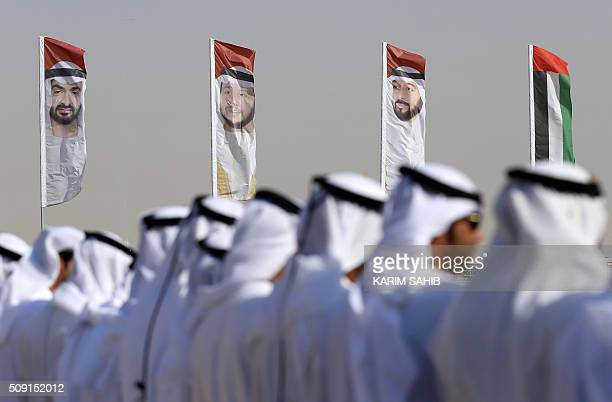 Emirati men perform a traditional dance in front of flags bearing portraits of Abu Dhabi's Crown Prince Sheikh Mohammed bin Zayed alNahyan Sheikh...