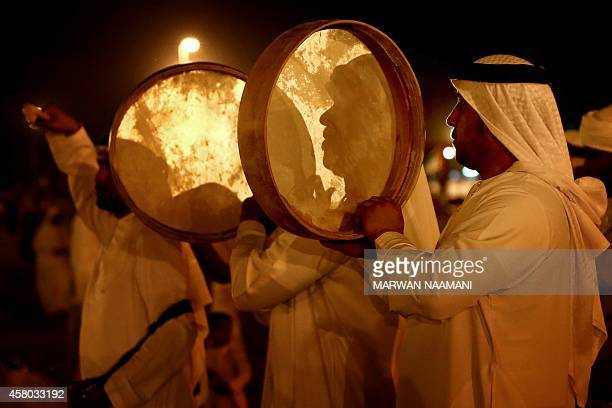 Emirati men play instruments as they perform a traditional dance late on October 28 2014 during a festival in the city of AlAin celebrating...