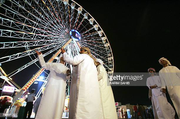 Emirati men stand in front of a giant ferris wheel at the Global Village in Dubai 19 December 2007 on the first evening of celebrations for the...