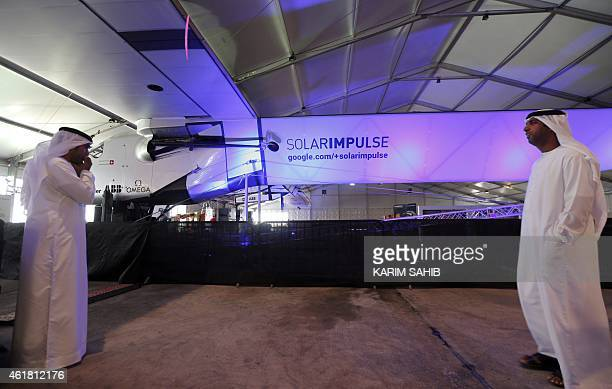 Emirati men stand near the Solar Impulse 2 the first solarpowered plane to be able to fly for several days and nights on January 20 2015 at an Abu...
