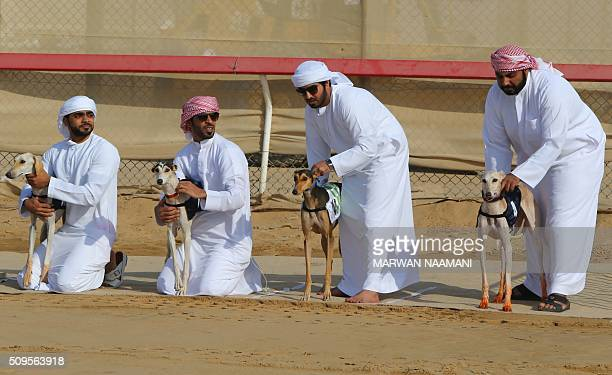 TOPSHOT Emirati men wait with their Arabian saluki dogs for the start of the traditional annual dog race in Shweihan on the outskirts of Abu Dhabi on...