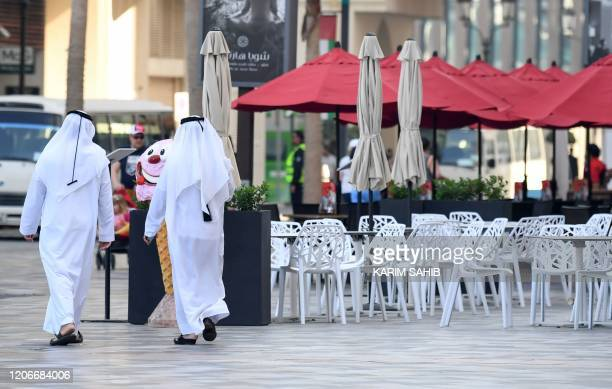 Emirati men walk along the empty beachside boulevard of Jumeirah Beach Residence which is usually crowded in the Gulf emirate of Dubai on March 12...