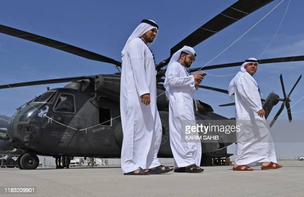 Emirati men walk past a Sikorsky CH53E Super Stallion at the Dubai Airshow on November 18 2019
