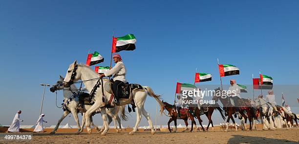 Emirati men waving their national flags ride horses during the 2015 Sheikh Zayed Heritage Festival in the capital Abu Dhabi as part of celebrations...