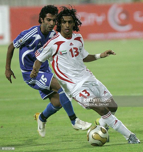 Emirati player Ahmed alJunaibi competes with Kuwait's Waleed Jumah during their group five World Cup qualifying football match in Kuwait City on June...