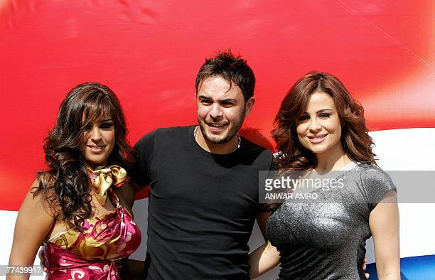 Emirati singer Ruwaida alMahruki Tunisian singer Ahmed alSharif and Lebanese singer Carole Samaha pose for a picture prior to the shooting of the...