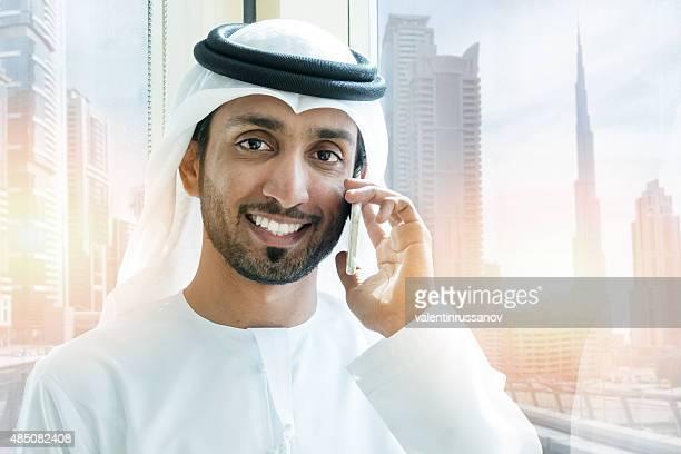 Emirati smiling businessmen in Dubai with mobile phone