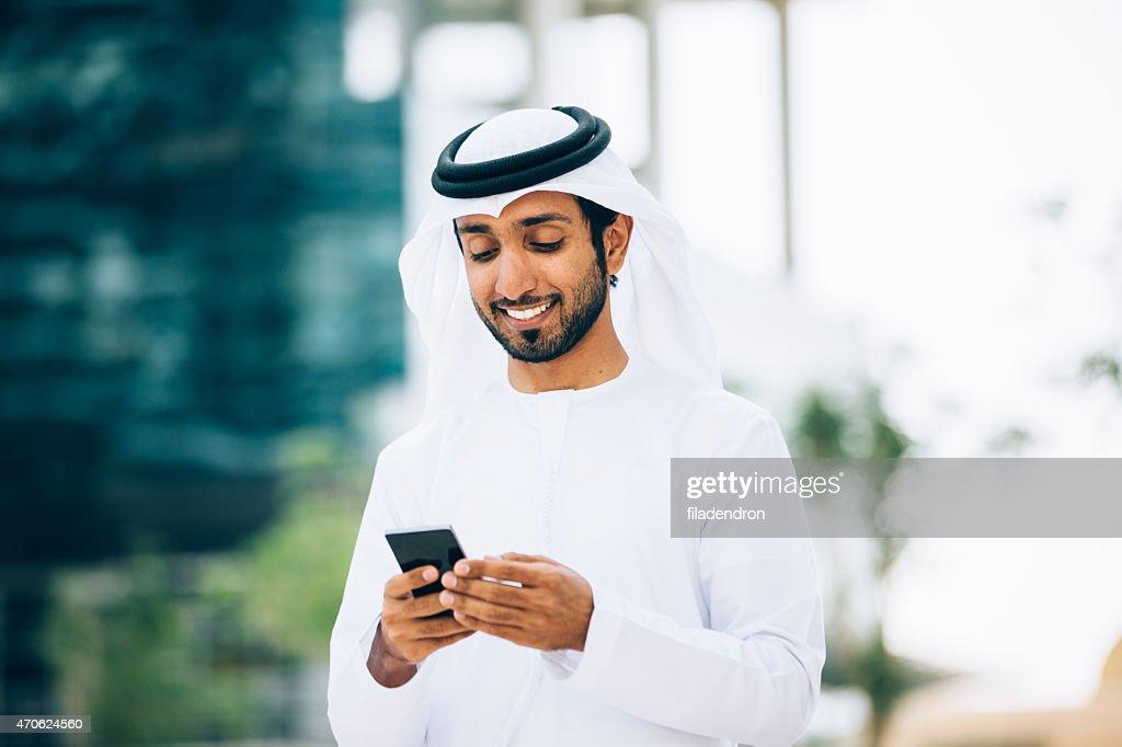 Emirati using a smart phone : Stock Photo