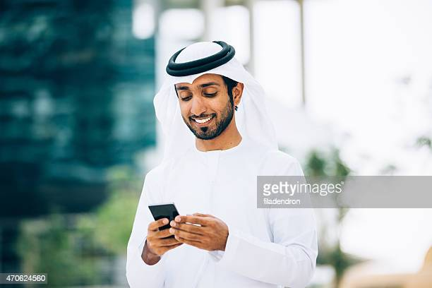 emirati using a smart phone - mobile phone stock pictures, royalty-free photos & images