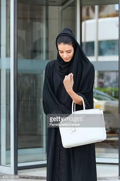 Emirati Woman Leaving Revolving Door Entrance and Looking in Handbag