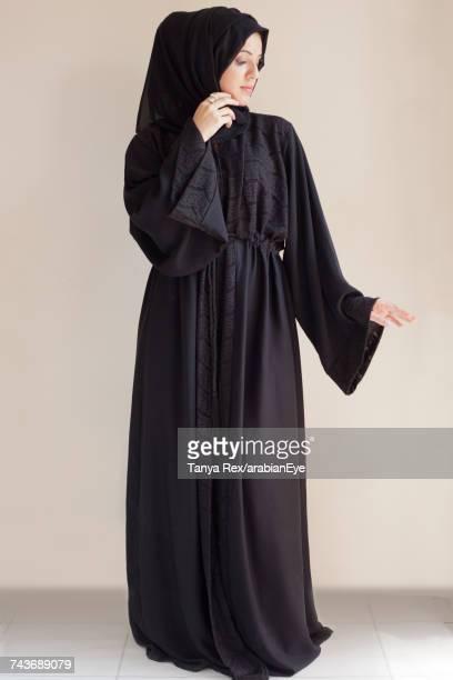 Emirati woman posing against white background.