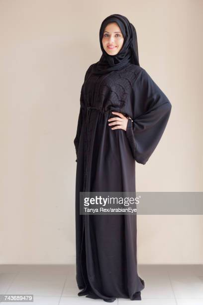 Emirati woman posing against white background.