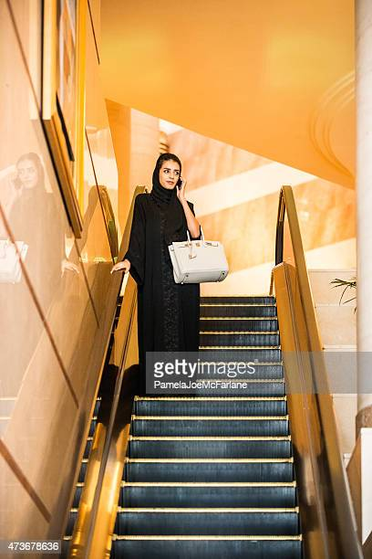 emirati woman talking on cellphone, riding escalator in luxury hotel - gold purse stock pictures, royalty-free photos & images