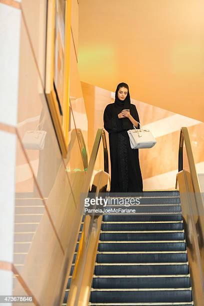 Emirati Woman Texting on Cellphone, Riding Escalator in Luxury Hotel