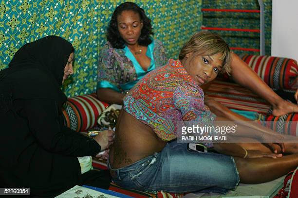 Emirati women make Henna tattoo on US tennis champions Serena and her sister Venus Williams , during a special ceremony of the WTA Dubai Women's Duty...