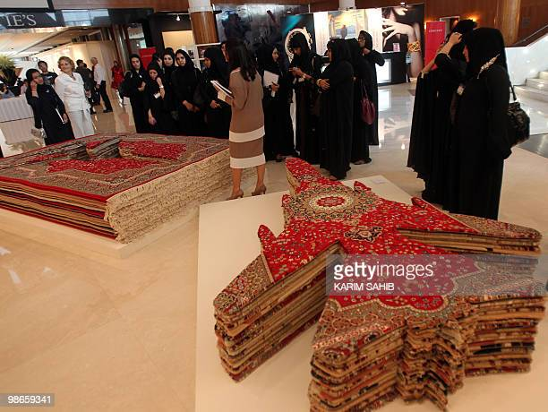 Emirati women stand next to an installation by Iranian artist Zakaria Farhad Moshiri titled the 'Flying Carpet' at Christie's in Dubai on April 25...