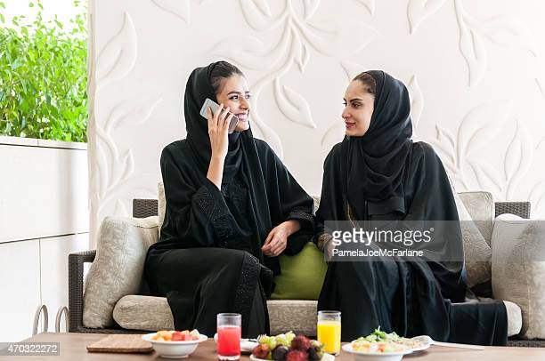 Emirati Women Wearing Abaya Eating Lunch and Talking on Cellphone