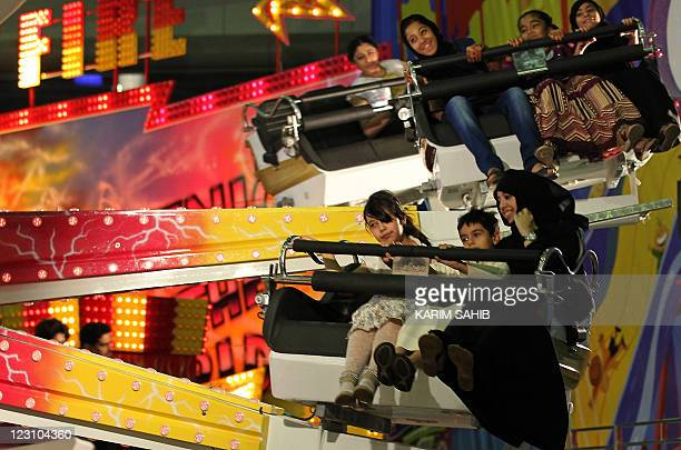 Emiratis enjoy a ride at a fun fair in Dubai's Modhesh City late on August 30 2011 as Muslims celebrate Eid alFitr which marks the end of the holy...
