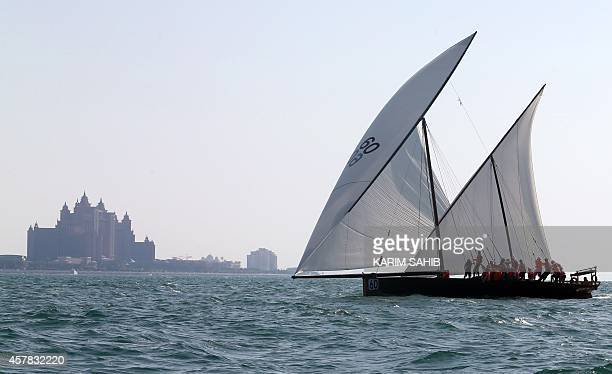 Emiratis sail traditional 60ft dhows towards the finishing line near Dubai's landmark Atlantis hotel during a race under the slogan Al Yamamah...