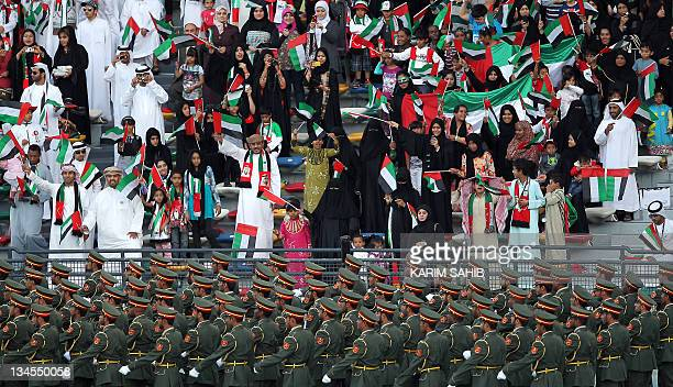 Emiratis wave their national flag as troops march during celebrations marking the 40th anniversary of the establishment of the United Arab Emirates...