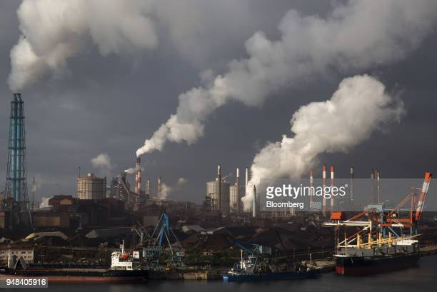 Emissions rise from chimneys as bulk carrier ships sit moored at the Nippon Steel Sumitomo Metal Corp plant in Kashima Ibaraki Japan on Wednesday...