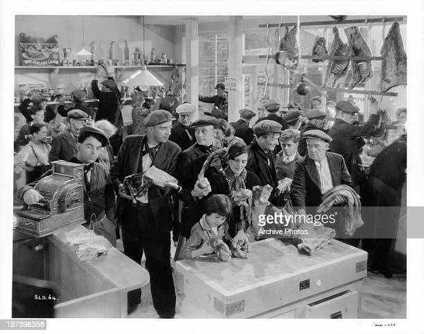Emlyn Williams steals the money from cash register while starving coal miners raid the butcher shop in a scene from the film 'The Stars Look Down'...