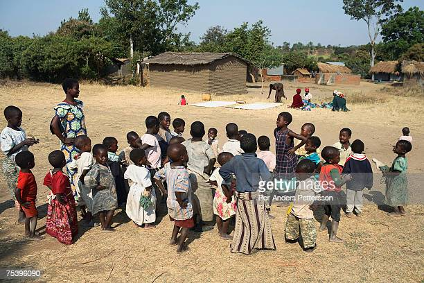 Emma Adam a teacher plays with about fifty orphans on August 21 2006 in Mphandula village about 30 miles outside Lilongwe Malawi Mphandula is a poor...