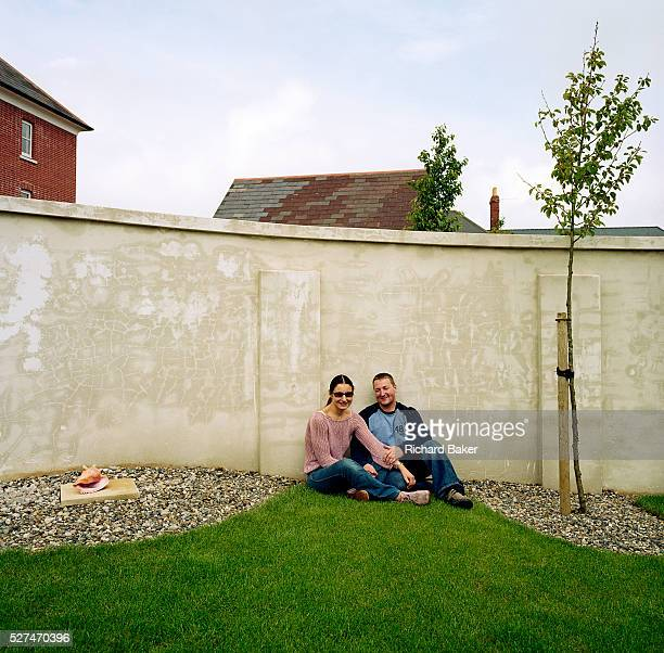 Emma and Martin are a young professional couple living in the experimental community village of Poundbury Dorset England Sitting in their landscaped...