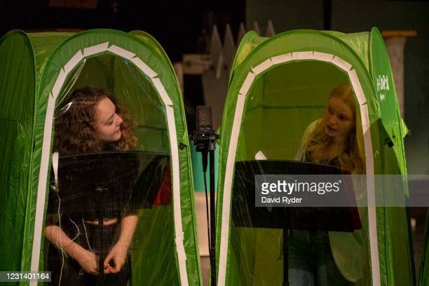 Emma Banker and Jessi McIrvin chat with each other before recording vocals in pop-up tents during choir class at Wenatchee High School on February...
