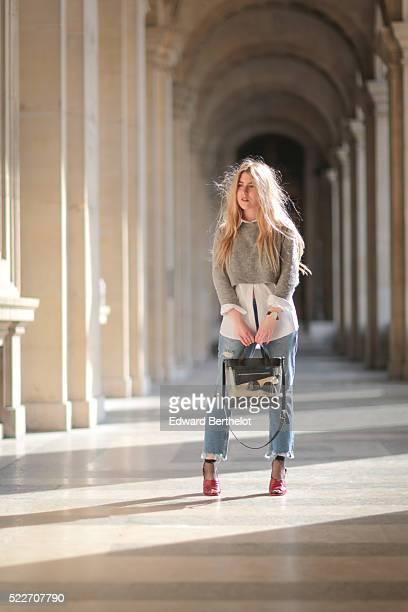Emma Bonneaud is wearing Zara red shoes Mango blue jeans a Wanted Gina white shirt an Asos gray pullover a Daniel Wellington watch a Zara bag and a...