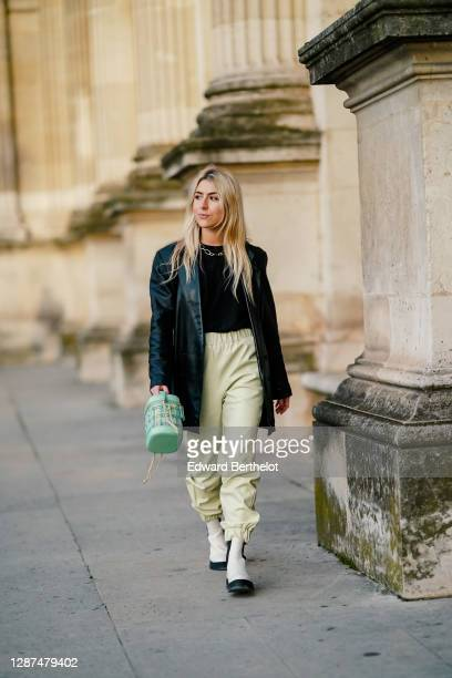 Emma Bonneaud wears a golden chain necklace a black leather oversized vintage jacket from Azzedine Alaia a black pullover pale green leather pants...