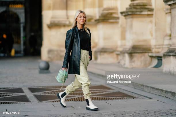 Emma Bonneaud wears a golden chain necklace, a black leather oversized vintage jacket from Azzedine Alaia, a black pullover, pale green leather pants...