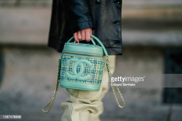 Emma Bonneaud wears black leather jacket, a green Chanel bag with embroidered logo and two parts made of tweed and leather, on November 24, 2020 in...
