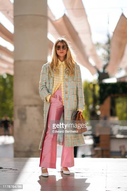 Emma Bonneaud wears sunglasses a yellow and white checkered shirt a beige and light turquoise blue tweed coat with brass buttons lustrous pink flare...