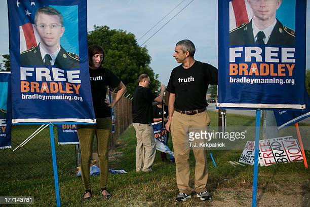 Emma Cape left and Patrick ConwayÊhold up signs as protesters with the Bradley Manning Support Network hold a vigil while waiting to hear Manning's...