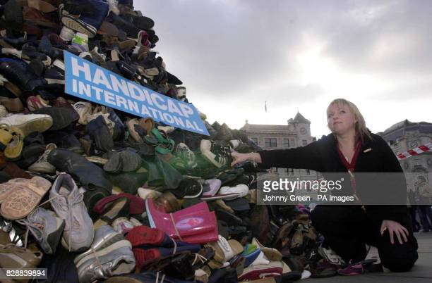 Emma Coleman from London contributes a pair of her old shoes to a pyramid of shoes that has been built to symbolise the horrifying loss of limb and...